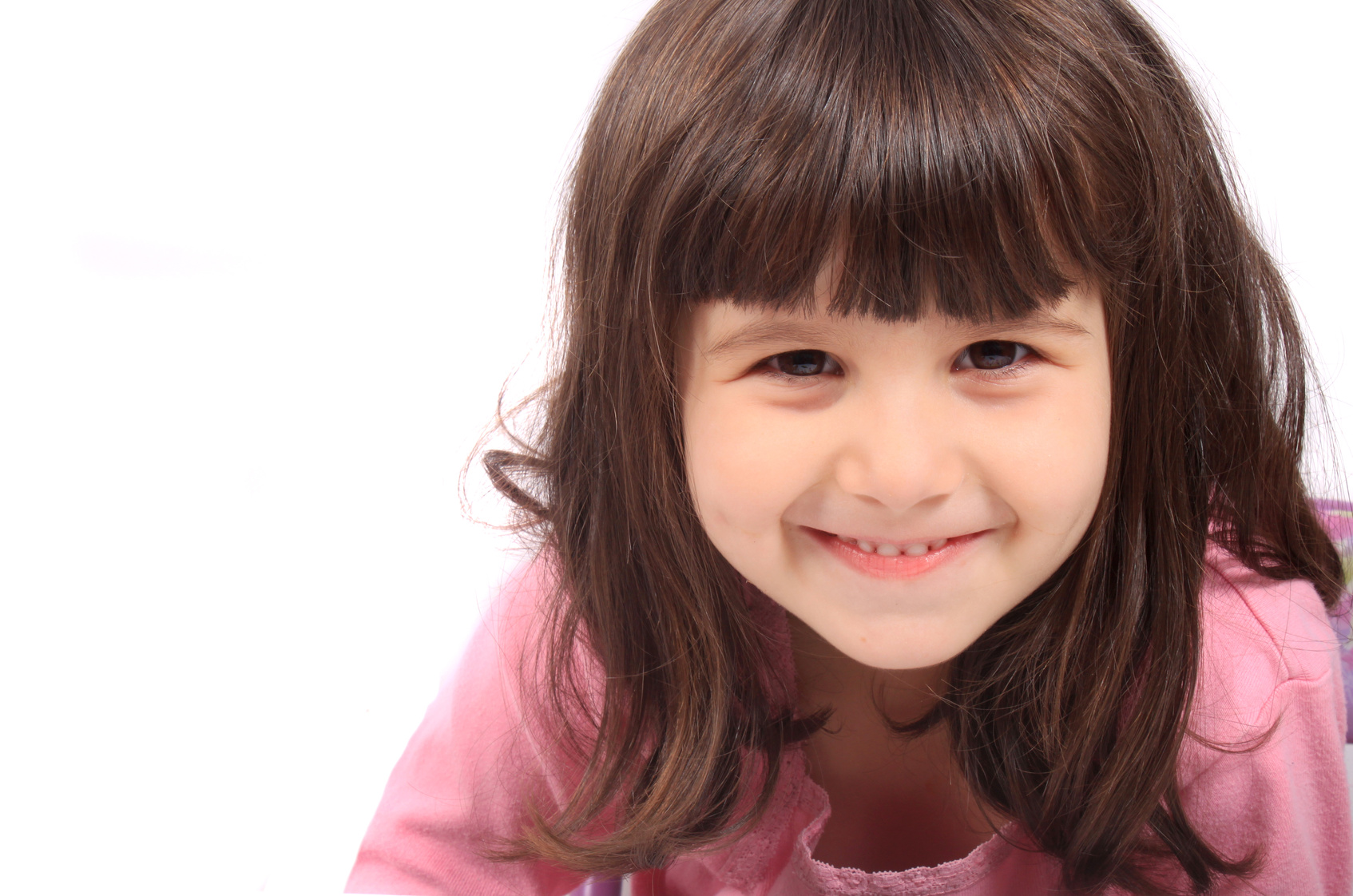Close up of little four year old brunette girl smiling on a white background
