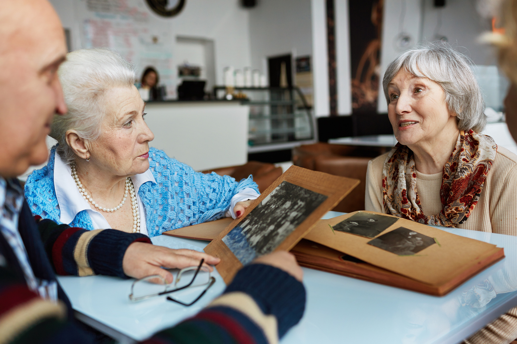 Friendly seniors talking while looking through photographs