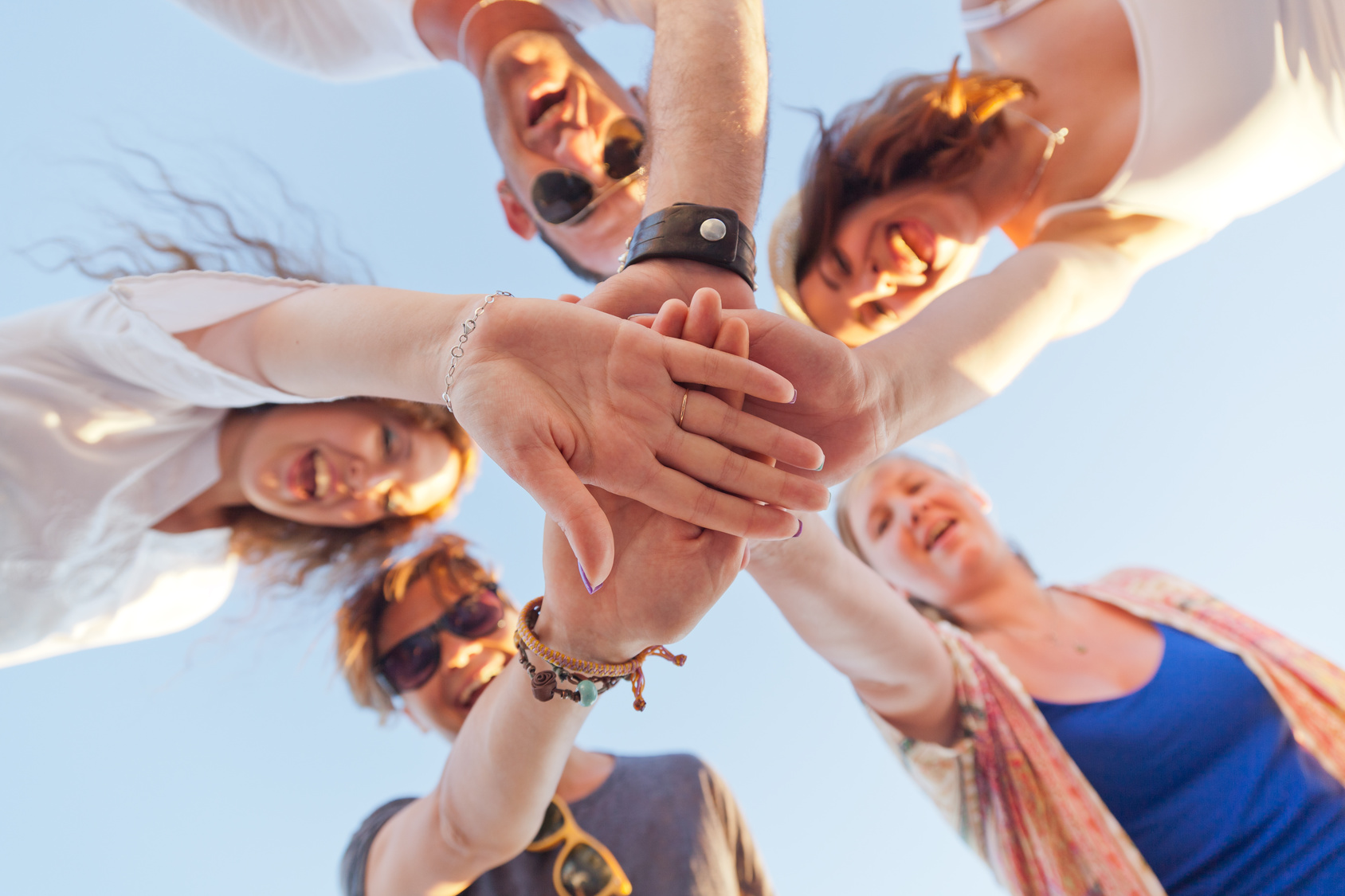 Hands close-up of friends joined together. The concept of friendship. Group of 5 young happy people
